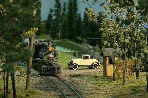 A cream '31 Model A Ford Coupe waits for the train to clear the crossing before proceeding into the town of Ojito